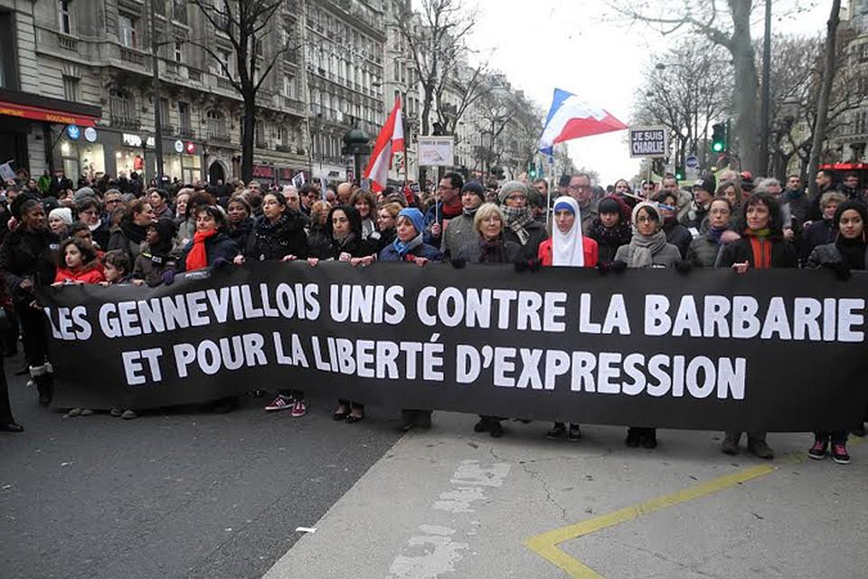 """Участники демонстрации держат плакат: """"Мы против варварства и за свободу выражения"""""""