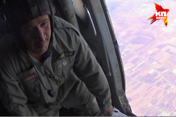 Один из летчиков открывает боковую дверь и вываливает один мешок с бумажками, которые красивой «струей» растекаются по небу
