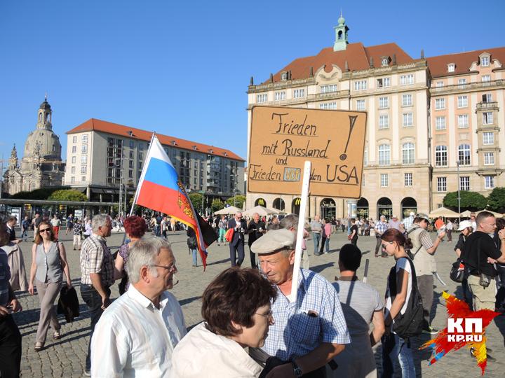 """Русский флаг и плакат """"Дружба с Россией"""" на митинге в Дрездене."""