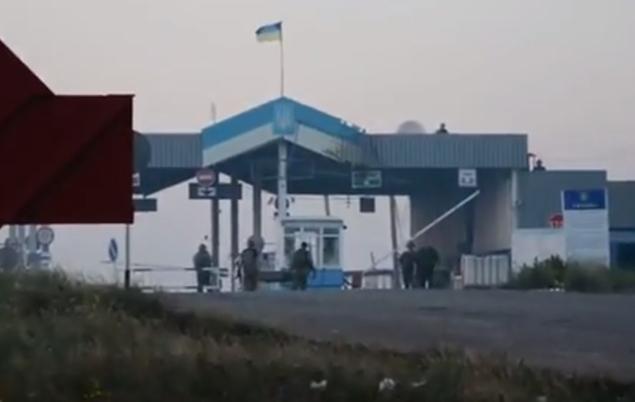 Украинские пограничники уносят раненных с пункта пропуска