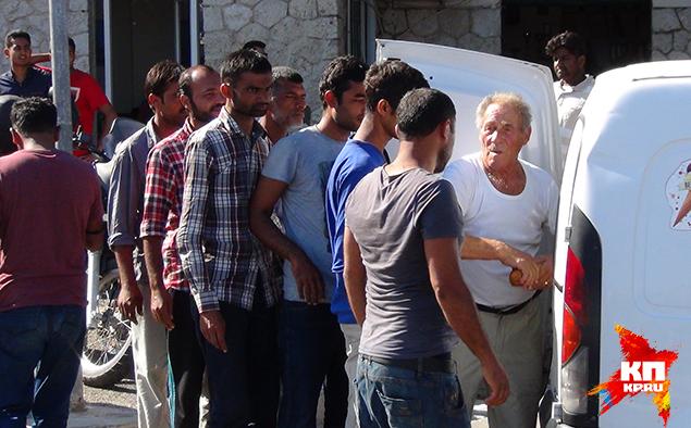 Дионисис Арванитатис раздает беженцам хлеб Фото: Владимир ДЕМЧЕНКО