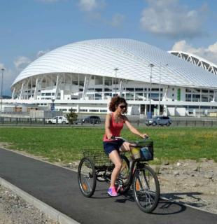 девушка едет на велосипеде вокруг стадиона фишт