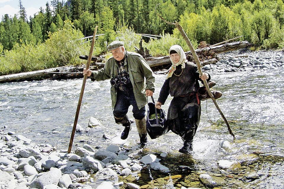 Василий Михайлович и отшельница Агафья пробираются через таежный ручей к ее заимке. Фото: Владимир ШЕЛКОВ/TASS