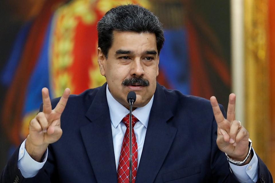 Президент Венесуэлы Николас Мадуро демонстрирует победные жесты на пресс-конференции.