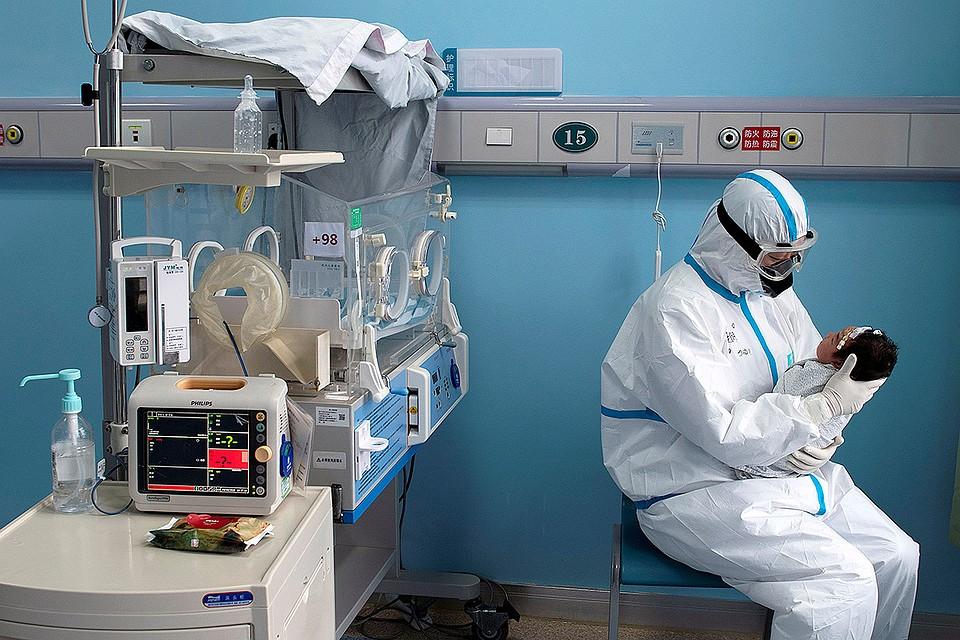 Медсестра с малышом, заразившимся коронавирусом, в госпитале китайского города Ухань.