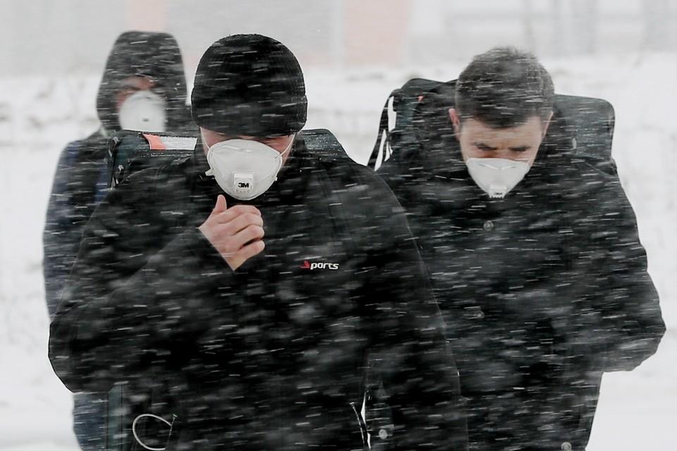 """Мужчины в защитных масках у здания многопрофильного медицинского центра """"Новомосковский"""", куда госпитализируют пациентов с подозрением на коронавирус COVID-19. Фото: Александр Щербак/ТАСС"""