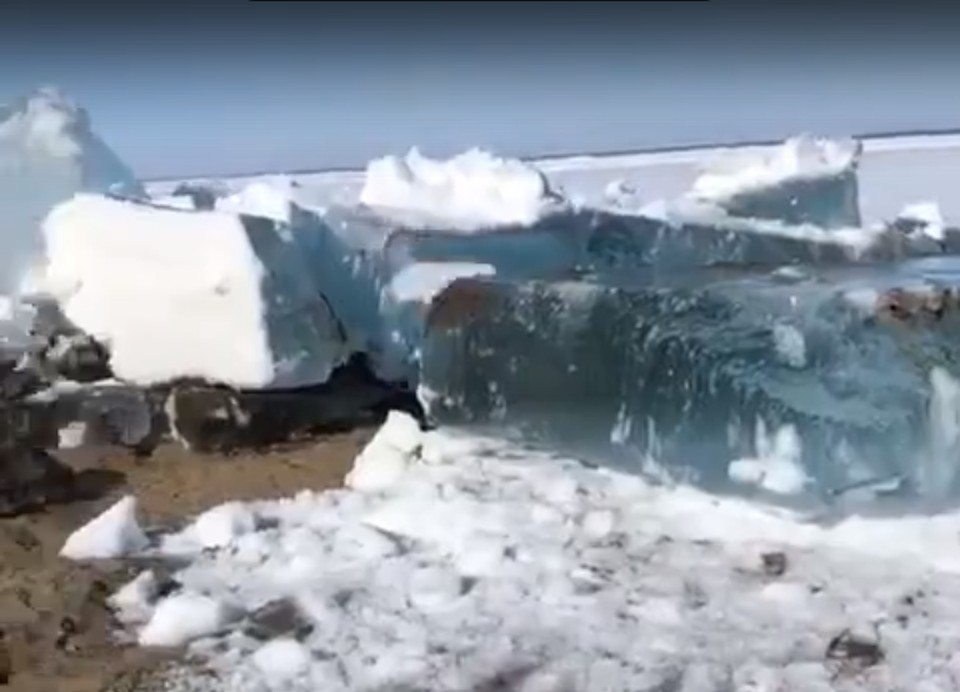 На видео лед загребает песчаный берег и глыбы льда переворачиваются. Скриншот видео