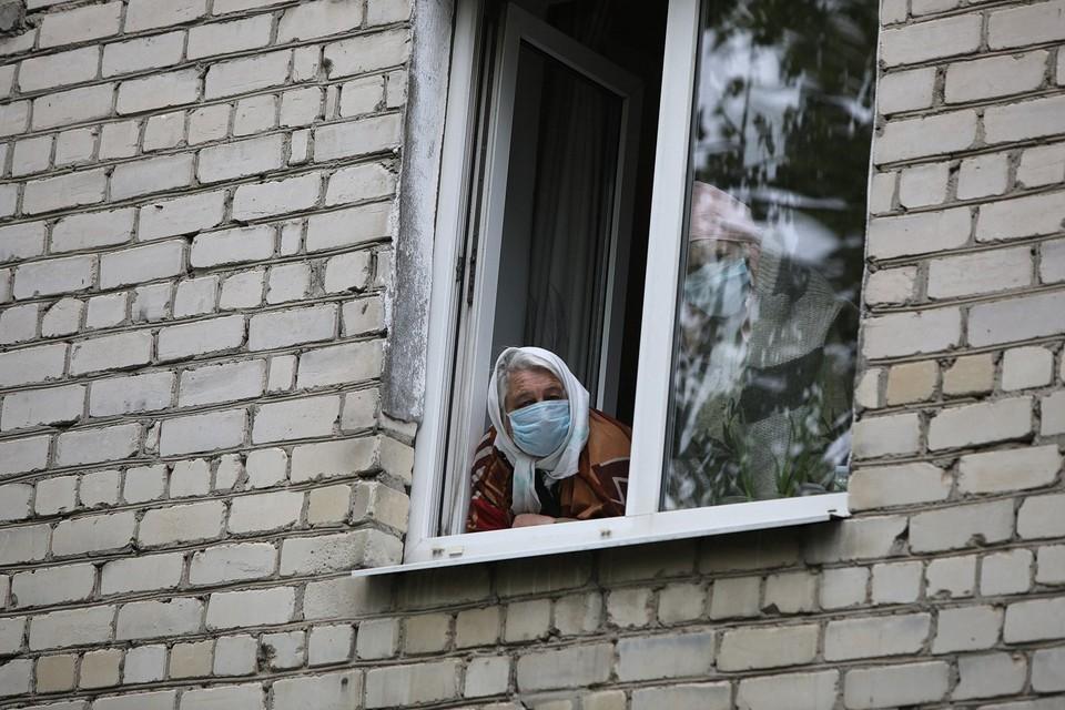 Женщины в масках смотрят в окно