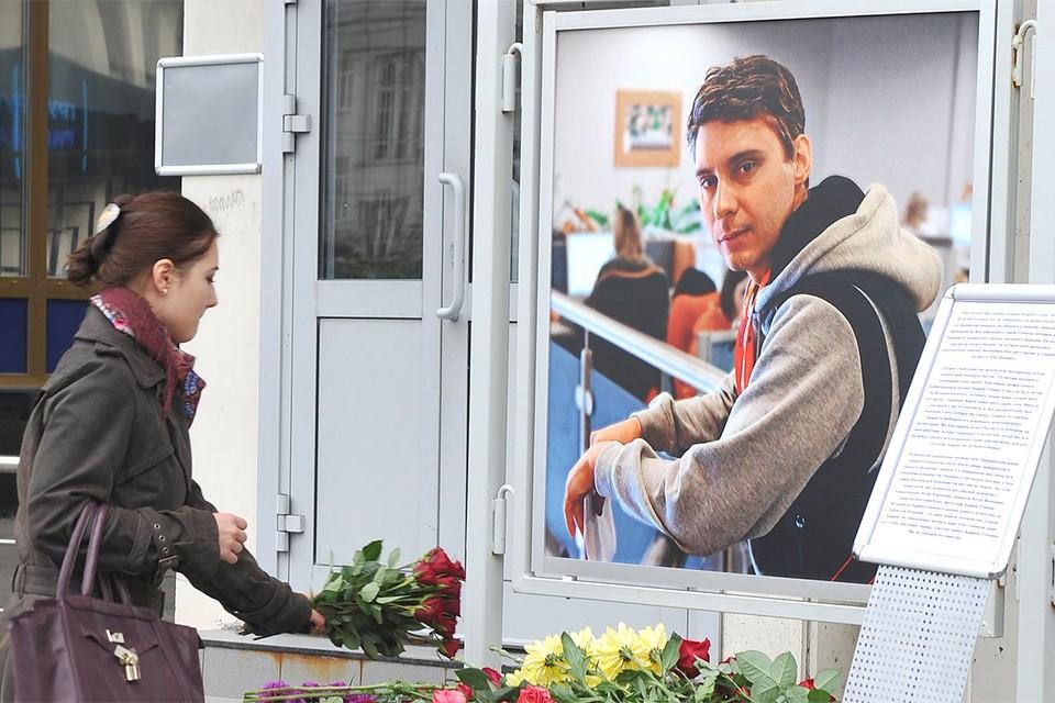 Люди приносят цветы в память о погибшем на Украине фотокорреспонденте МИА `Россия сегодня` Андрее Стенине к зданию агентства, сентябрь 2014 года.
