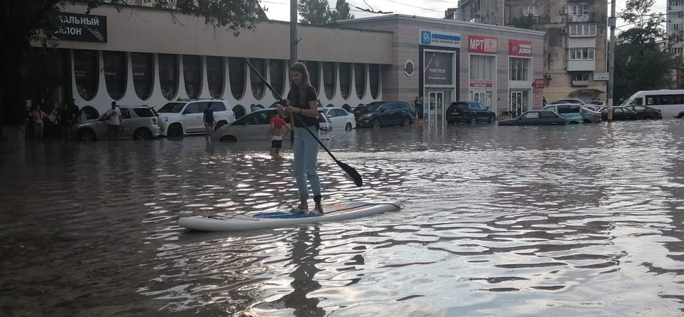 Девушка устроила заплыв на доске по затопленному проспекту Ленина в Новороссийске. Фото: Юлиана Староверова