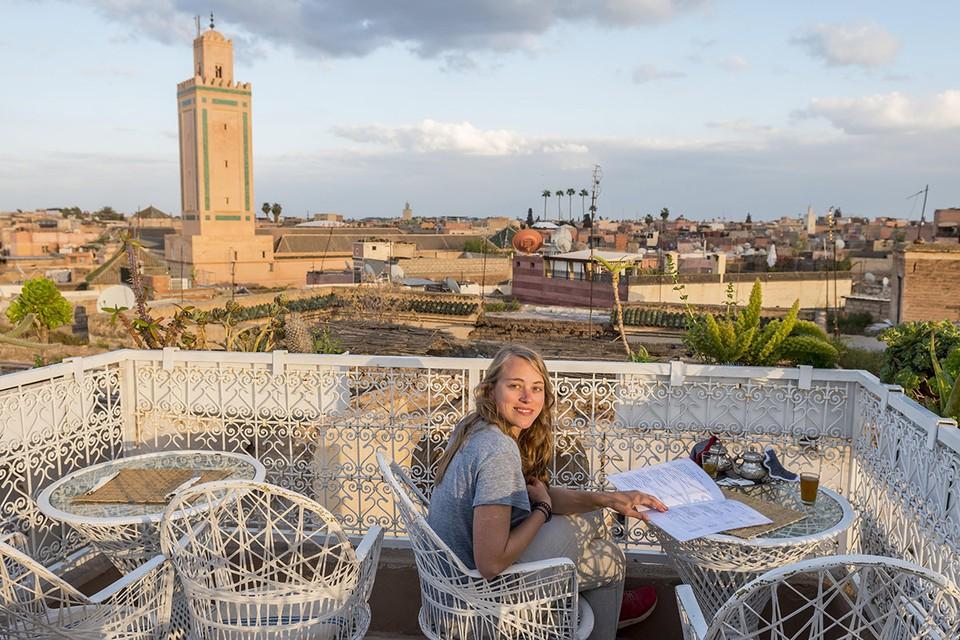 Туристка завтракает в кафе с видом на центр города Марракеш.