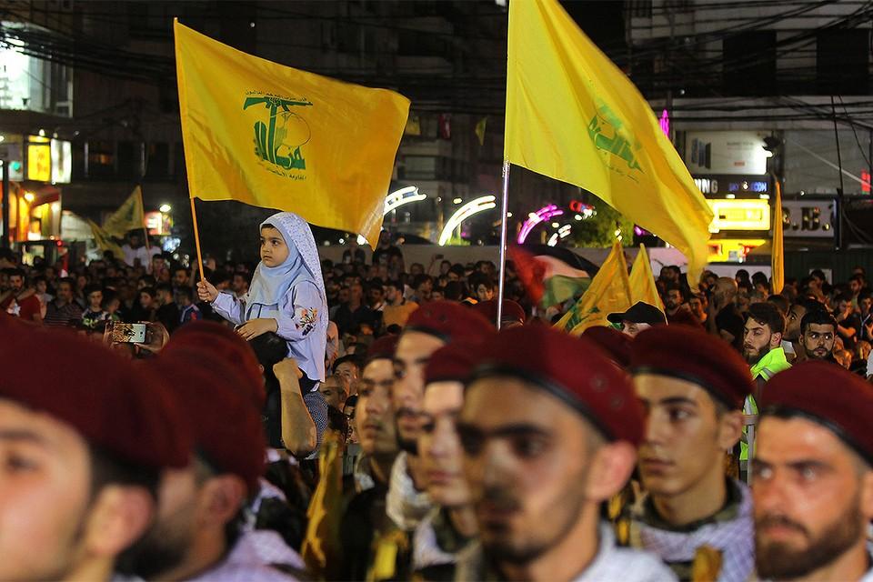 """Девочка с флагом """"Хезболлы"""" на митинге в Бейруте."""