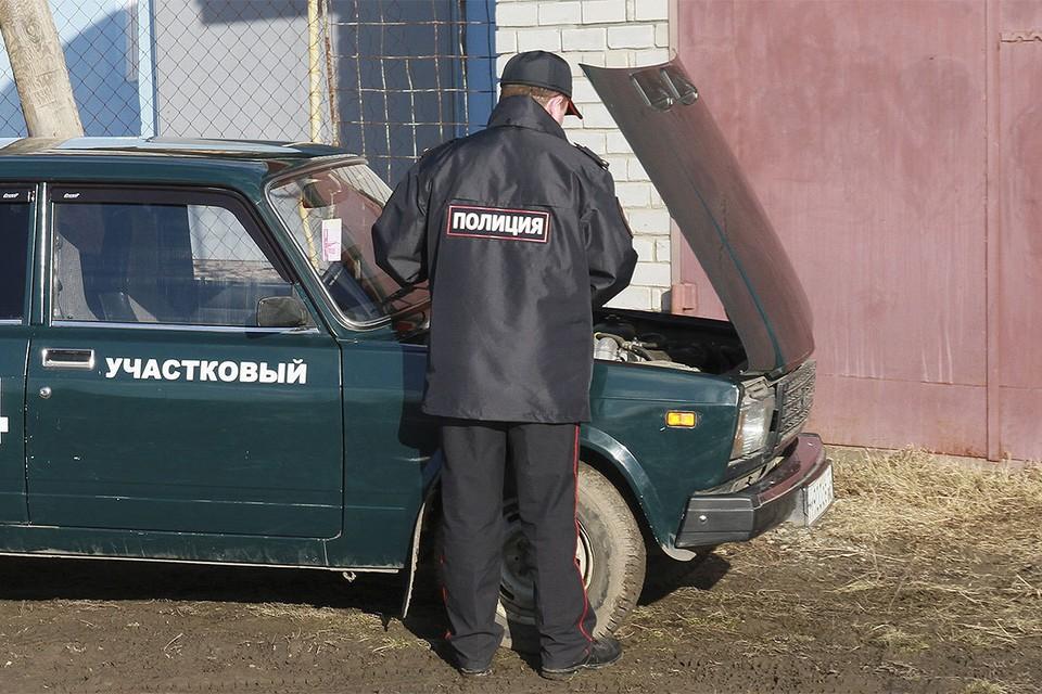 Алтайский край. Участковый полицейский у служебного автомобиля.