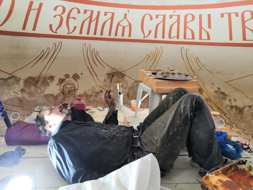 Андрей на лесах. Художник работает лежа.