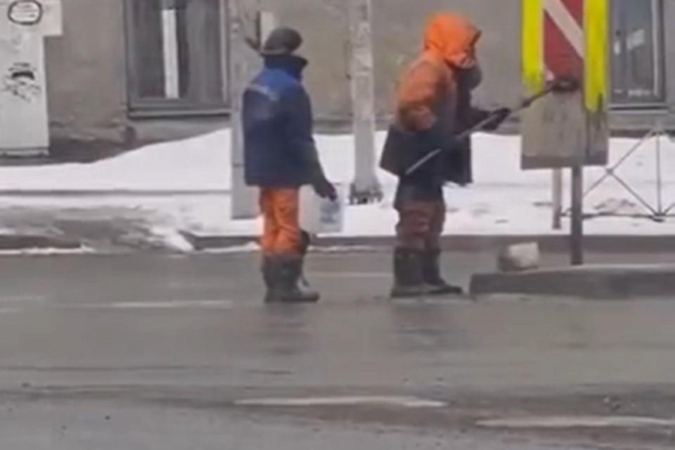 В Новосибирске коммунальщики моют дорожные знаки водой из лужи. Фото: стоп-кадр.