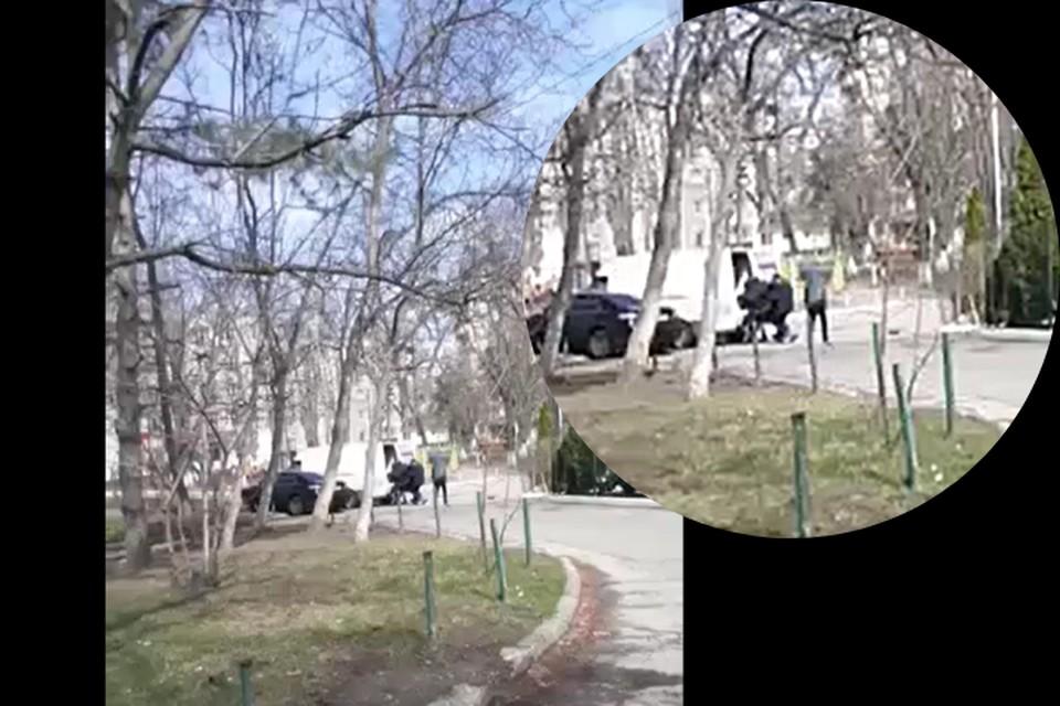 Трое в черном заталкивают похищенного человека в бусик.