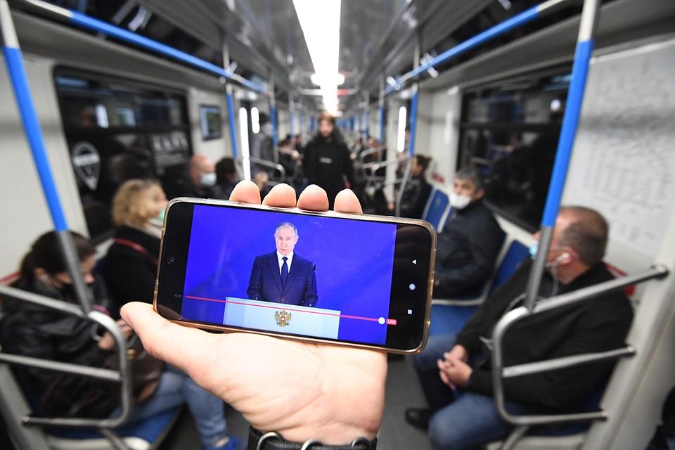 Пассажиры Московского метро смотрят выступление президента России с ежегодным посланием Федеральному собранию РФ.