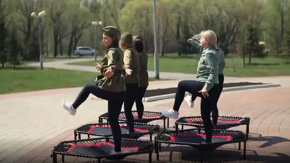 Девушки в имитации военных гимнастерок и спортивных штанах решили поздравить омичей, прыгая возле мемориала погибшим людям. Фото: скриншот видео