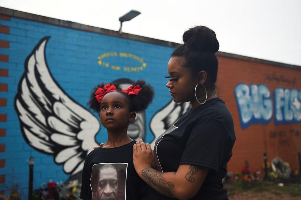 Мать и дочь позируют перед фреской Джорджа Флойда в преддверии годовщины смерти Флойда в Хьюстоне.