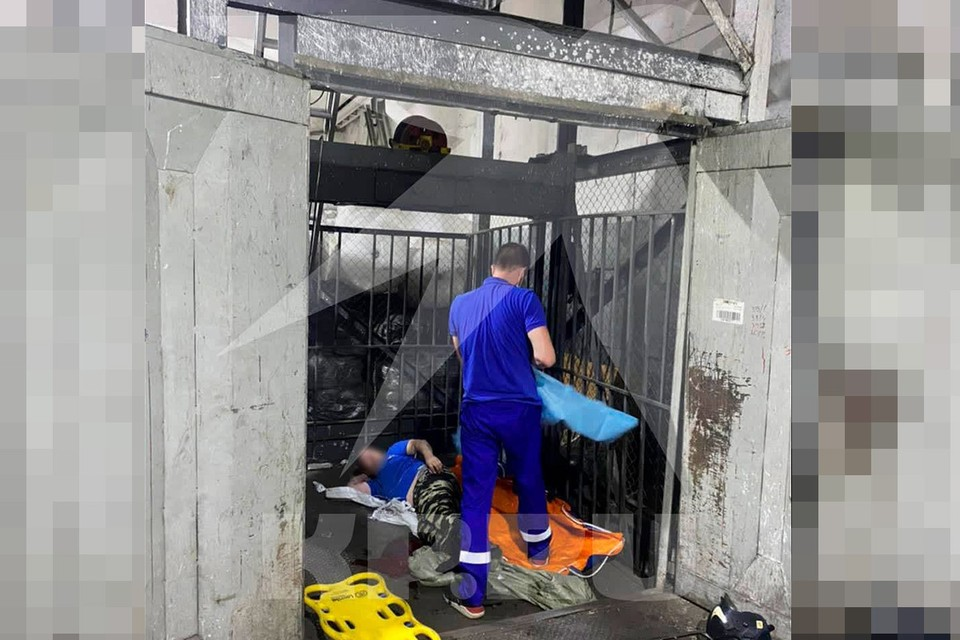 Медик оказывает первую помощь рабочим, пострадавшим в результате падения лифта в складском помещении на Иловайской улице.