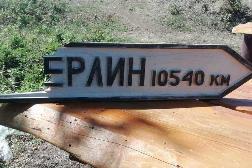 Сломанная табличка «Берлин 10540 км». Источник: Telegram-канал @nashkholmsk