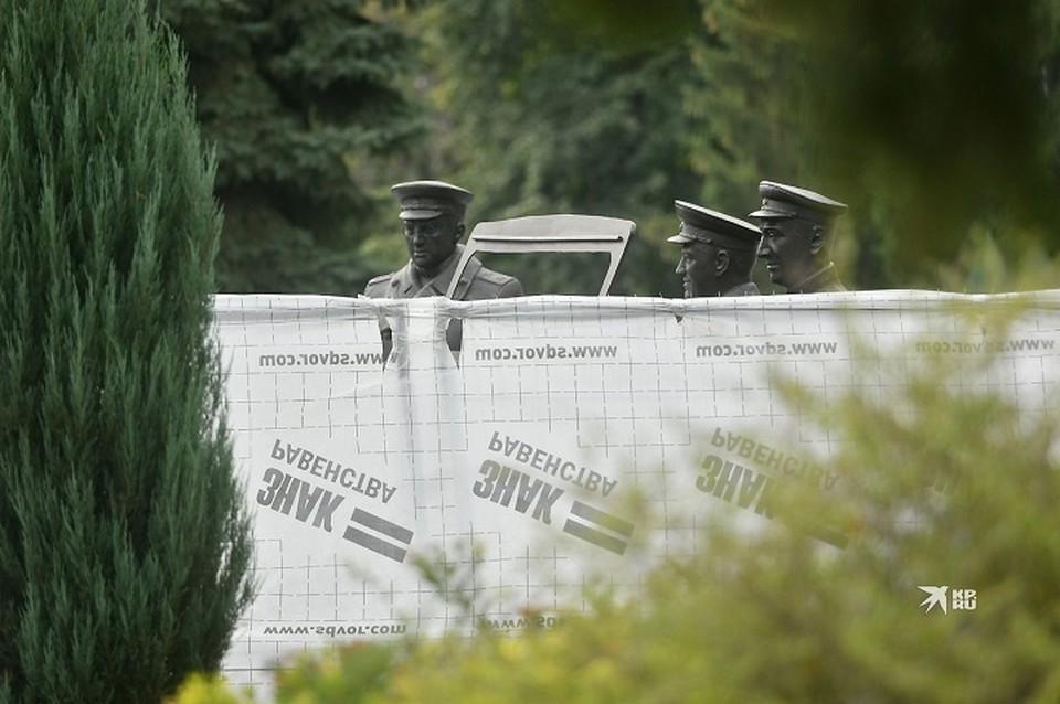 Пока памятник скрыт за ограждением и брезентом