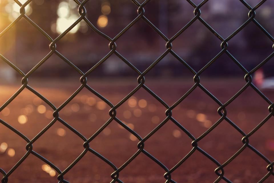 Школьник перелезал через металлический забор стадиона и повис на пробитой руке. Фото: Pexels