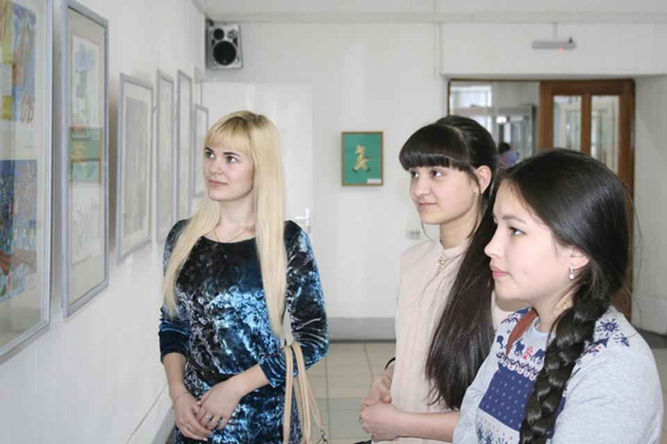 Школьники с интересом знакомятся с экспонатами выставки в фойе университета