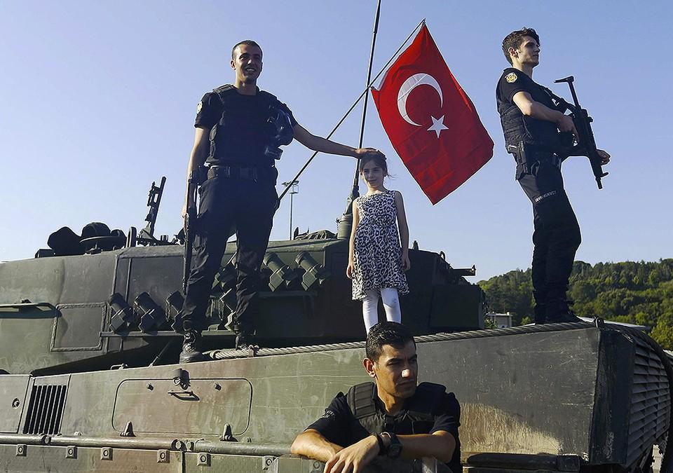 Полицейские на танке, который был оставлен мятежными военными.