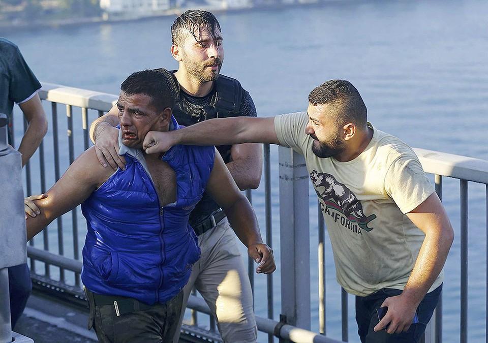 Захваченный офицер-мятежник, одетый в штатское, получает удар в лицо от жителя Стамбула.