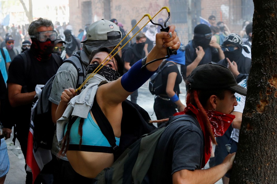 Студенты ведут обстрел позиций полиции во время уличных беспорядков в Сантьяго, Чили.