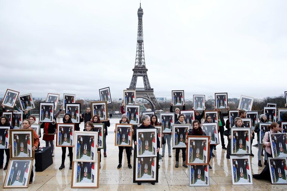 Французское активисты вышли к Эйфелевой башне и держат в руках перевернутые портреты Макрона в знак протеста против изменений климата.