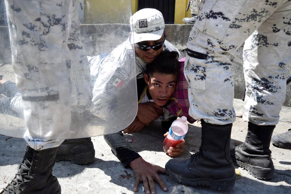 Мигранты пытаются просочиться через ряды мексиканских полицейских, окруживших один из лагерей нелегалов возле границы с США.