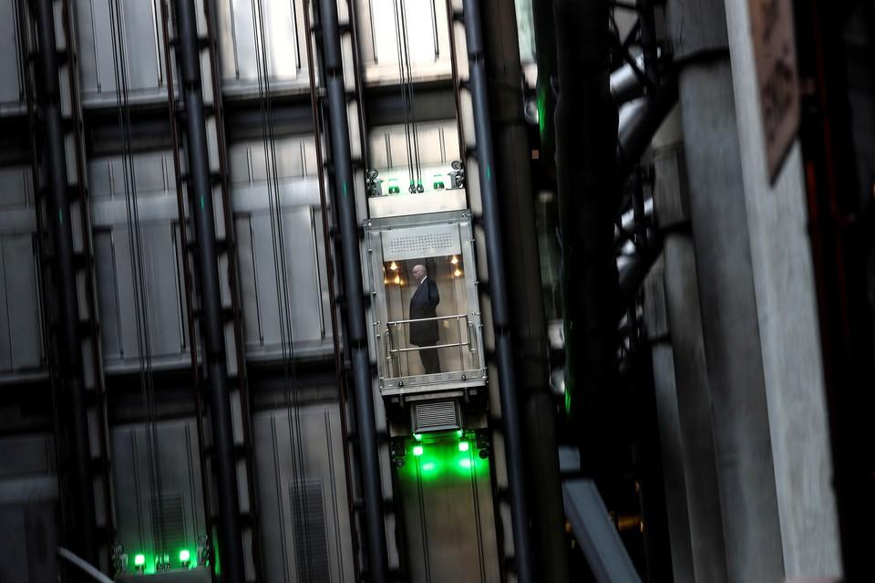 Работник офиса в деловом здании Лондона поднимается на нужный этаж.
