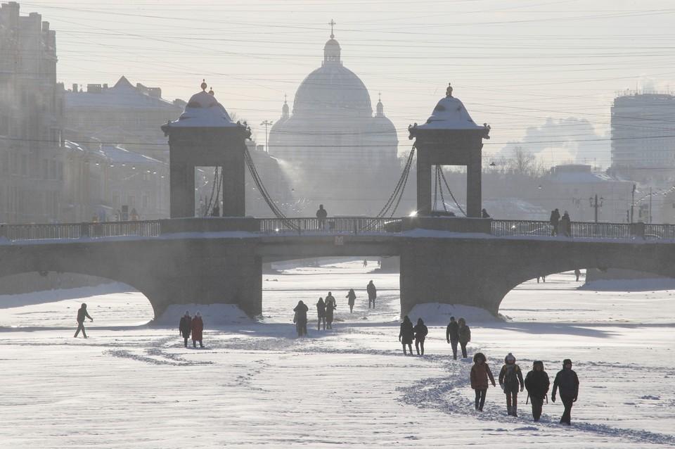Жители Санкт-Петербурга прогуливаются по замерзшим каналам города.