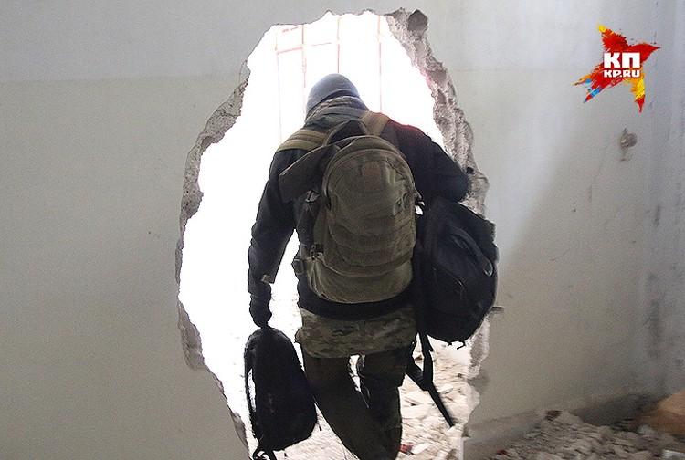 """Военкоры """"Комсомолки"""" ныряют в выбитый в стене переход между зданиями."""