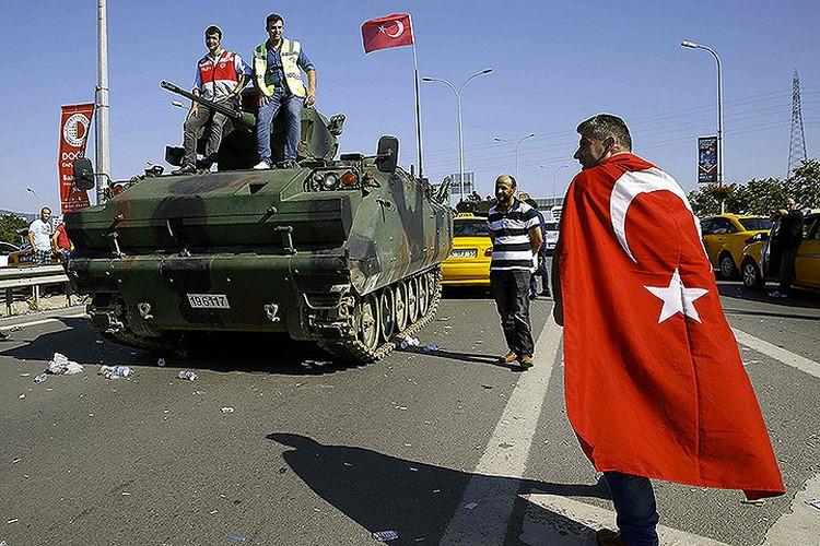 Сторонники Эрдогана разгуливают рядом с брошенной военной техникой по Босфорскому мосту.