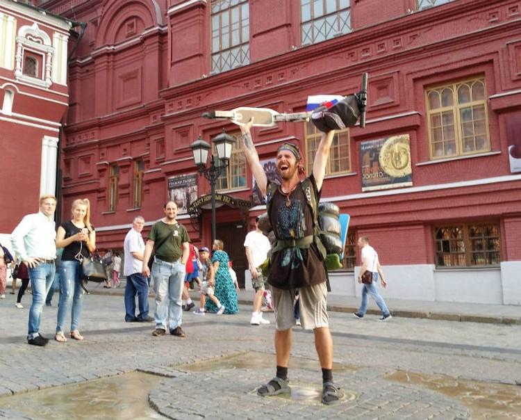Уставший, но счастливый Александр на нулевом километре в Москве.