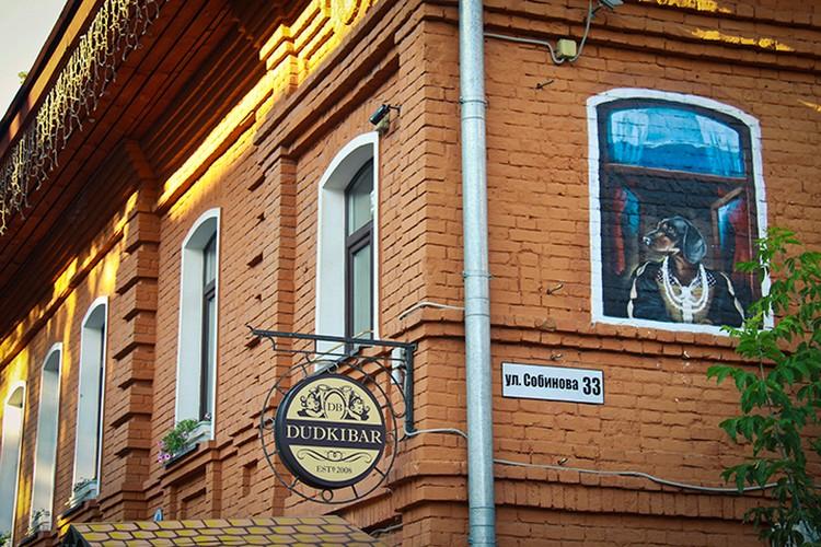 Сразу за углом из нарисованного окна на втором этаже «Дудки-бара» на город смотрит такса в жемчугах.