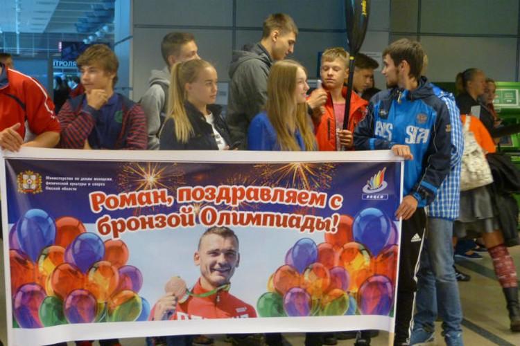 Юные гребцы ждали своего героя с огромным плакатом.