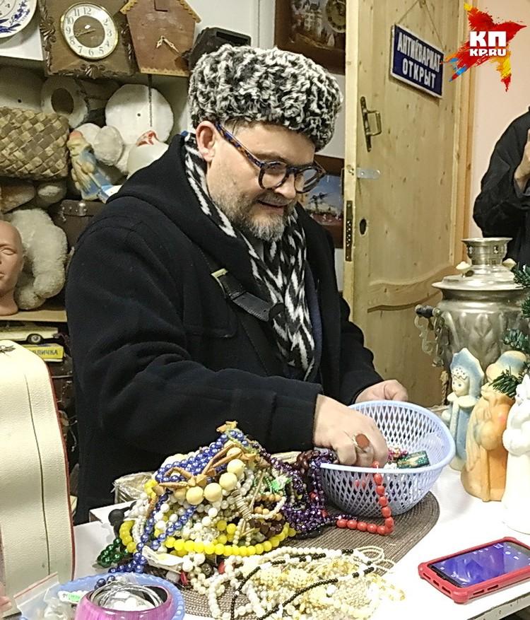 Александр Васильев выискивает в антикварной лавке бижутерию.