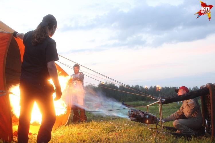 Два человека открывают основание шара, куда пилот направляет огонь горелки