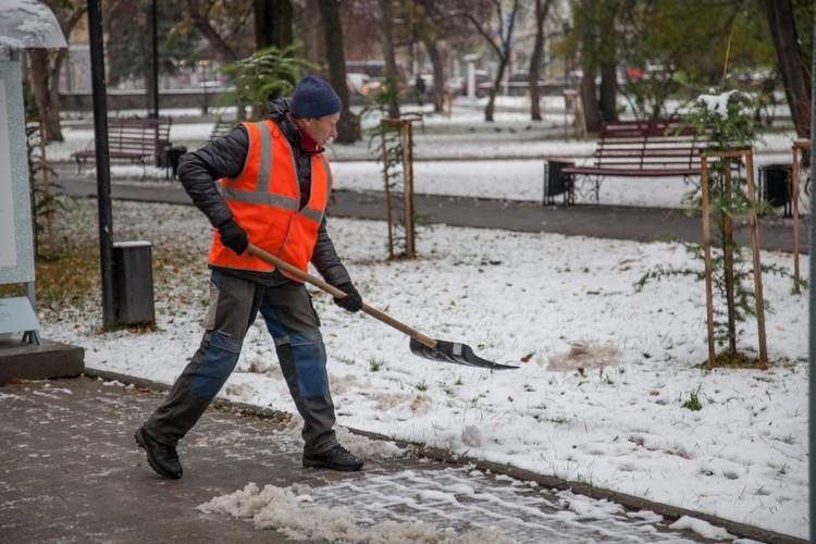 Дворник чистит тротуар.