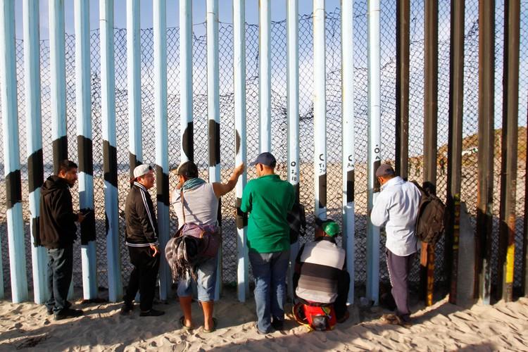 Первые беженцы попытались перелезть через забор на границе Мексики и США.