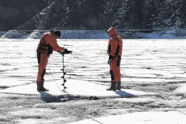 Спасатели разрушают ледяные глыбы и пилят вмерзшие в них деревья