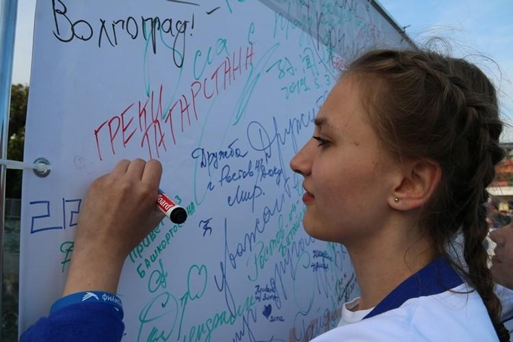Молодежь охотно расписывала на огромной открытке поздравления участникам и пожелания удачи.