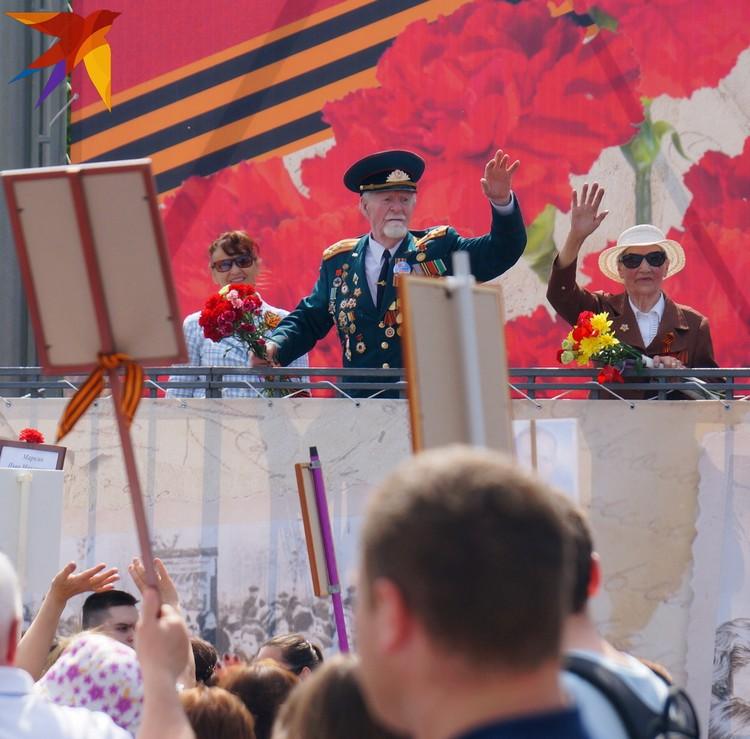 Ветераны и участники шествия приветствуют друг друга.