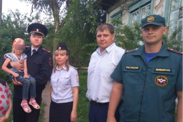 Полицейский Максим Медведский (держит девочку на руках) передал ее бабушке и дедушке. Фото: ГУ МВД России по Иркутской области.
