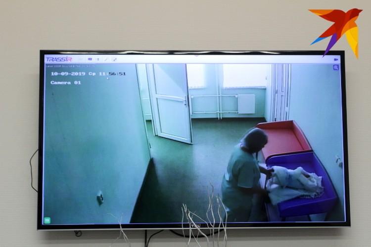 На мониторе можно увидеть, как пеленают малыша перед выпиской