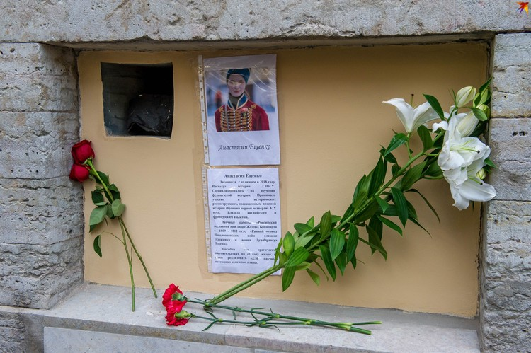 У мрачного «мемориала» уже появились цветы: четыре алых розы и белые орхидеи